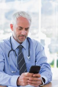 Doctor typing a text message on his smartphone